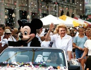 Barbara Taylor Bradford and Mickey Mouse acknowledge the large crowd from an open motorcade at Walt Disney World in Florida, as confetti showers them on the parade route.