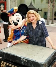 At Disney's MGM Studios, Barbara Taylor Bradford smiles after placing her hands in a cement mold as part of the 'Walk of Fame' exhibit, while Mickey Mouse playfully looks on.