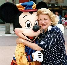 Barbara Taylor Bradford receives a hug from Mickey Mouse following her handprint ceremony at Disney's MGM Studios in Florida. The impression of her handprints remain on permanent display.