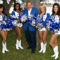 Bob Bradford is perfectly color coordinated as he raises the pompoms with the Cowboys Cheerleaders